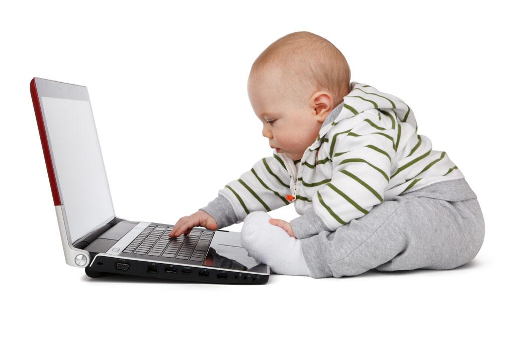 リビングで真剣にパソコンで遊ぶ双子の女の子の赤ちゃん